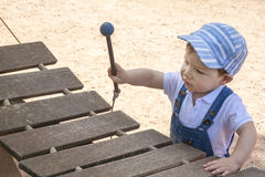Baby boy playing wooden xylophone at playground. Baby boy playing wooden xylophone. He is at playground Royalty Free Stock Photos