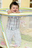 Baby boy in playpen. Smiling baby boy standing in a playpen Royalty Free Stock Images