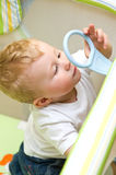 Baby boy in playpen. Playing with plastic handle Royalty Free Stock Photo