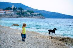 Baby boy plays with dog. Cute baby boy plays with dog pet on beach shore on summer day on blue sea Royalty Free Stock Images