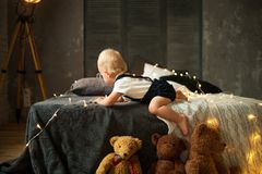 Baby boy plays with garland of glowing light bulbs. Baby boy crawls at the bed and plays with garland of glowing light bulbs next to the toys royalty free stock images