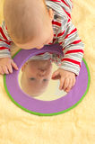Baby boy plays with mirror Stock Images