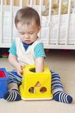 Baby boy plays nesting blocks at home against white bed Royalty Free Stock Photo