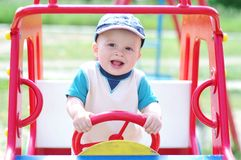 Baby boy plays on playground outdoors. Baby boy age of 9 months plays on playground outdoors Stock Photo
