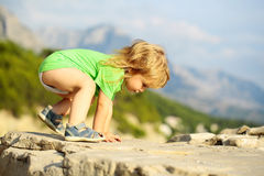 Baby boy plays on rocks. Cute baby boy child with curly blond hair in green shirt plays on rocks on sunny summer day on natural background Stock Photos