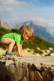 Baby boy plays on rocks. Cute baby boy child with curly blond hair in green shirt plays on rocks on sunny summer day on natural background Stock Photo
