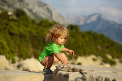 Baby boy plays on rocks Stock Photos