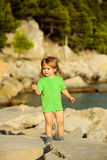 Baby boy plays at sea. Cute baby boy child with curly blond hair in green shirt plays at rocky sea beach on summer day Stock Photos