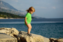 Baby boy plays at sea. Cute baby boy child with curly blond hair in green shirt plays at rocky sea beach on summer day Royalty Free Stock Images