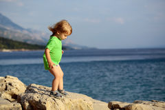Baby boy plays at sea. Cute baby boy child with curly blond hair in green shirt plays at rocky sea beach on summer day Royalty Free Stock Image