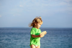 Baby boy plays at sea. Cute baby boy child with curly blond hair in green shirt plays with stone at sea beach on summer day Stock Photo