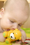 Baby boy plays with toy. On colourful carpet Royalty Free Stock Photos