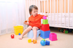 Baby boy plays toys sitting on potty Royalty Free Stock Image
