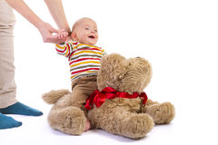 Baby boy on plush dog on white Royalty Free Stock Images
