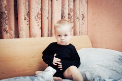Baby boy posing on parents' bed in bedroom. Baby boy sitting and posing on parents' bed in bedroom royalty free stock photography