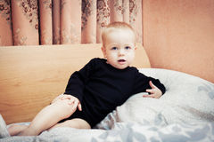 Baby boy posing on parents' bed in bedroom