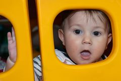 Baby boy is posing through a plastic window.  royalty free stock photo