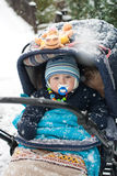 Baby boy in pram during winter snow fall. Baby boy sitting in pram during winter snow fall Royalty Free Stock Photography
