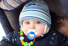 Baby boy in pram during winter snow fall Royalty Free Stock Images