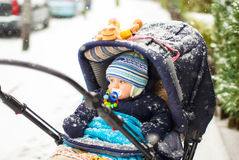 Baby boy in pram during winter snow fall. Cute baby boy in warm clothes in pram during winter snow fall on cold winter day. Happy carefree childhood Royalty Free Stock Photo