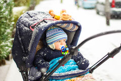 Baby boy in pram during winter snow fall. Cute baby boy in warm clothes in pram during winter snow fall on cold winter day. Happy carefree childhood Stock Photo
