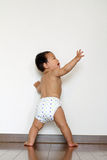 Baby boy pulling up to stand Stock Photo