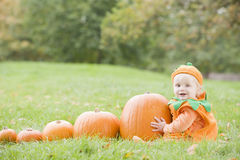 Baby boy in pumpkin costume with pumkins stock photo