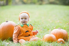 Baby boy in pumpkin costume with pumpkins royalty free stock photography