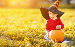 Baby boy with pumpkin outdoors in halloween Royalty Free Stock Photos