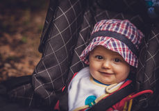 Baby boy in a pushchair. Portrait of a happy and adorable baby boy 6 months old in his pushchair Royalty Free Stock Photo