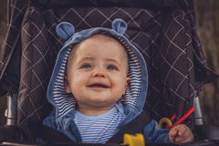 Baby boy in a pushchair. Portrait of a happy and adorable baby boy 6 months old in his pushchair Stock Images
