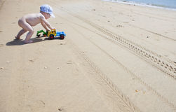 Baby boy pushing his beach toys over the sand Royalty Free Stock Photography