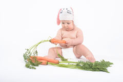 Baby boy in rabbit hat with fresh carrot Stock Images