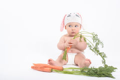 Baby boy in rabbit hat holding carrot looking with distrust. Baby boy in rabbit hat holding fresh carrot looking with distrust, on white background Royalty Free Stock Image