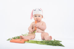 Baby boy in rabbit hat holding fresh carrot Royalty Free Stock Image