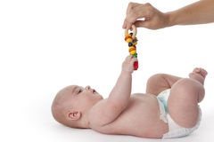Baby boy reaching for a colored toy Stock Photos