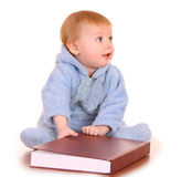 Baby boy read big red book. Stock Images