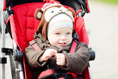 Baby boy in red stroller Stock Photos