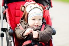 Baby boy in red stroller Stock Photos