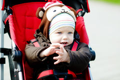 Baby boy in red stroller Royalty Free Stock Photography