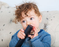 Baby boy with remote Stock Photography