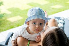 Baby boy resting above mother's shoulder and looks out with focused blue eyes curious expression stock images