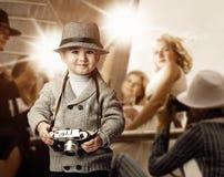 Baby boy with retro camera. Over photo shoot background Stock Photos