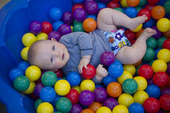 Baby boy with reusable nappy diaper in ball pond. A blue eyes baby boy plays in a clam shell ball pond while wearing a cloth nappy Royalty Free Stock Photo