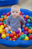 Baby boy with reusable nappy diaper in ball pond. A blue eyes baby boy plays in a clam shell ball pond while wearing a cloth nappy Stock Images