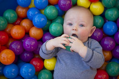 Baby boy with reusable nappy diaper in ball pond. A blue eyes baby boy plays in a clam shell ball pond while wearing a cloth nappy Royalty Free Stock Images