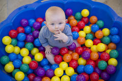 Baby boy with reusable nappy diaper in ball pond. A blue eyes baby boy plays in a clam shell ball pond while wearing a cloth nappy Stock Photos