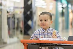 Baby boy rides in a trolley through a shopping center. Royalty Free Stock Image
