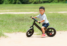 Baby boy riding with balance bicycle. Asian young little boy at outdoor stock images