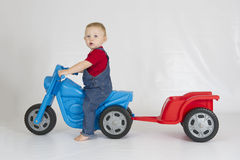 Baby boy riding his plastic scooter and trailer. A toddler enjoys his scooter and trailer set while wearing denim dungarees Stock Photo